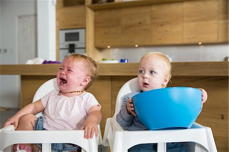 Male and female twin toddlers in high chairs Stock Photo - Premium Royalty-Free, Code: 649-08060398
