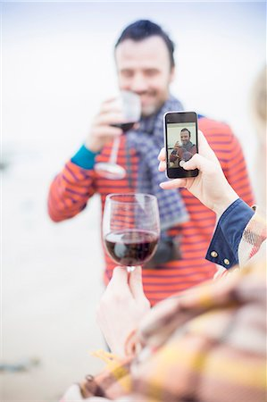 Couple outdoors, drinking wine, woman taking photograph of man Stock Photo - Premium Royalty-Free, Code: 649-08060503