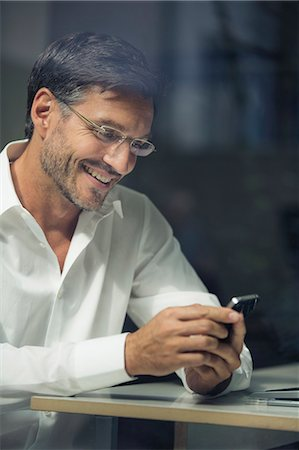 Businessman texting on smartphone by office window Stock Photo - Premium Royalty-Free, Code: 649-08060688