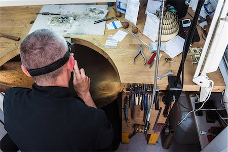 Overhead view of jewellery craftsman at workbench Stock Photo - Premium Royalty-Free, Code: 649-08060760