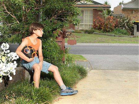 preteen boys playing - Sullen boy sitting on suburban wall holding soccer ball Stock Photo - Premium Royalty-Free, Code: 649-08060814