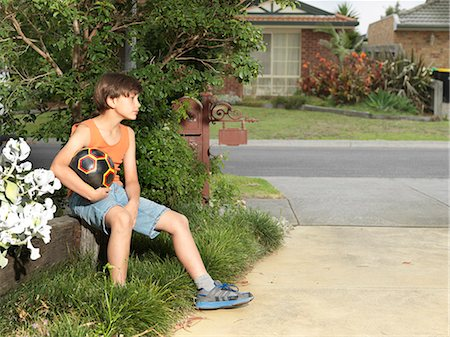 preteen boys playing - Sullen boy sitting on suburban wall holding soccer ball Stock Photo - Premium Royalty-Free, Code: 649-08060814