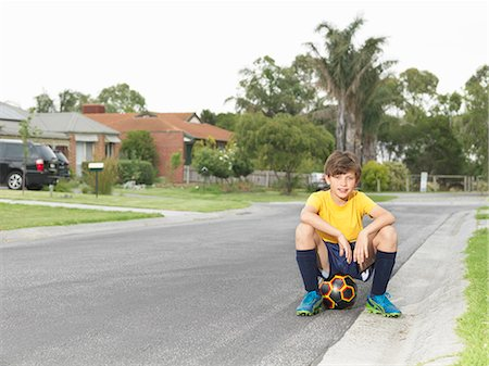 Portrait of boy sitting on soccer ball on suburban road Stock Photo - Premium Royalty-Free, Code: 649-08060815