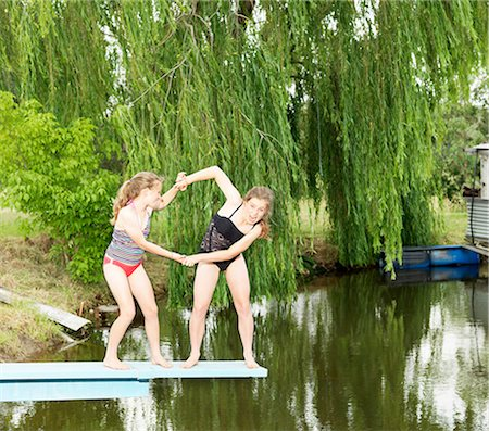 Two sisters play-fighting on diving board over lake Stock Photo - Premium Royalty-Free, Code: 649-08060884