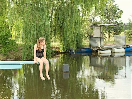 Teenage girl sitting on diving board over lake Stock Photo - Premium Royalty-Free, Code: 649-08060882