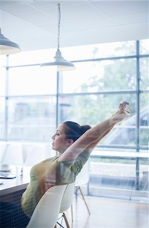 stretch - Young woman stretching at desk Stock Photo - Premium Royalty-Free, Code: 649-08084508