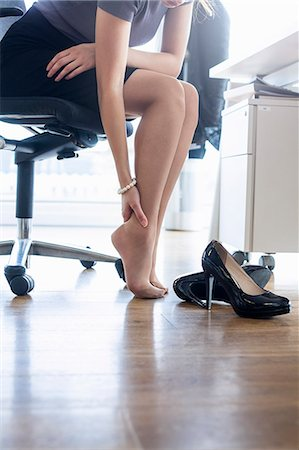 foot massage - Neck down view of businesswoman massaging ankle at office desk Stock Photo - Premium Royalty-Free, Code: 649-08084685