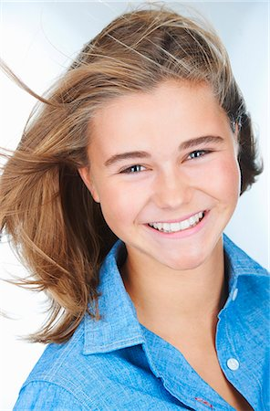 Portrait of smiling teenage girl with hair blowing Stock Photo - Premium Royalty-Free, Code: 649-08084727