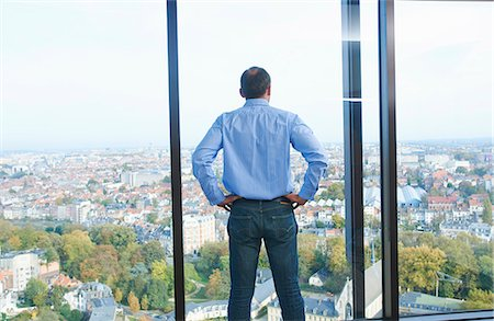 Rear view of businessman looking from office window at Brussels cityscape, Belgium Stock Photo - Premium Royalty-Free, Code: 649-08084748