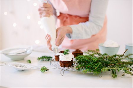 Woman icing chocolate cupcakes with whipped cream Stock Photo - Premium Royalty-Free, Code: 649-08084792