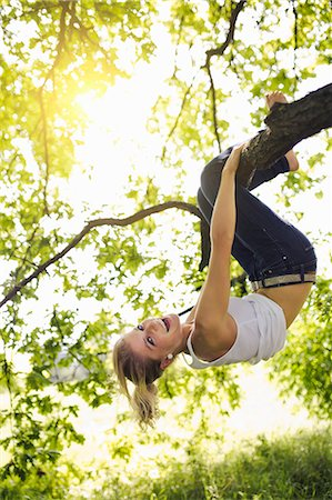 dangling - Young woman hanging upside down and holding onto tree branch Stock Photo - Premium Royalty-Free, Code: 649-08084878