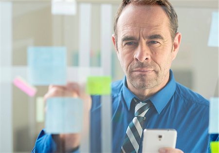 Businessman with smartphone sticking notes on office glass wall Stock Photo - Premium Royalty-Free, Code: 649-08084886