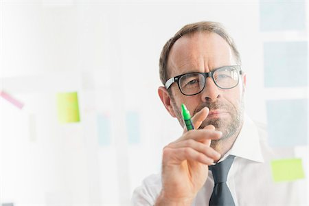 self adhesive note - Businessman working on ideas at office glass wall Stock Photo - Premium Royalty-Free, Code: 649-08084881