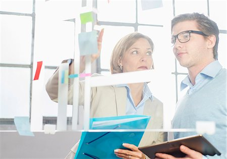 Businessman and woman pointing at idea notes on office glass wall Stock Photo - Premium Royalty-Free, Code: 649-08084897