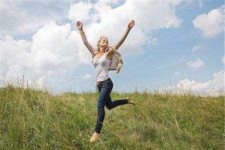 Young woman running through field with arms in air Stock Photo - Premium Royalty-Free, Code: 649-08085013