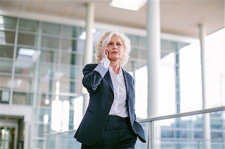 Mature businesswoman walking along walkway, using mobile phone, low angle view Stock Photo - Premium Royalty-Free, Code: 649-08085076