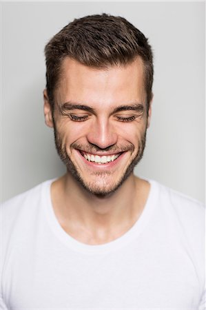 Close up portrait of smiling young man with eyes closed Stock Photo - Premium Royalty-Free, Code: 649-08085111