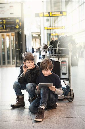 Two brothers sitting on airport luggage trolley looking at digital tablet Stock Photo - Premium Royalty-Free, Code: 649-08085142
