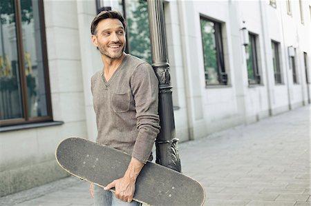 Mature man leaning against lamppost holding skateboard Stock Photo - Premium Royalty-Free, Code: 649-08085229