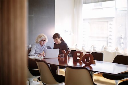 Two mature businesswomen using laptop at boardroom table Stock Photo - Premium Royalty-Free, Code: 649-08085230