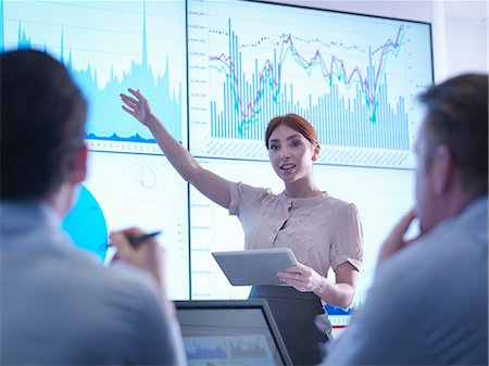 presentation (displaying) - Businesswoman making presentation to colleagues in front of graphs on screen Stock Photo - Premium Royalty-Free, Code: 649-08085254