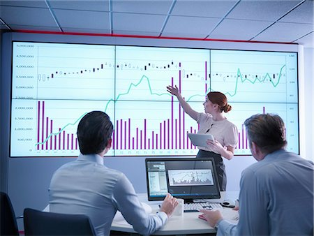 Businesswoman making presentation to colleagues in front of graphs on screen Stock Photo - Premium Royalty-Free, Code: 649-08085255