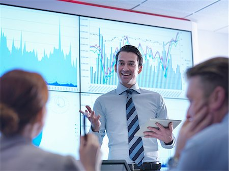 displaying - Businessman making presentation to colleagues in front of graphs on screen Stock Photo - Premium Royalty-Free, Code: 649-08085253