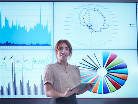 Portrait of businesswoman making presentation in front of graphs on screen Stock Photo - Premium Royalty-Free, Code: 649-08085263