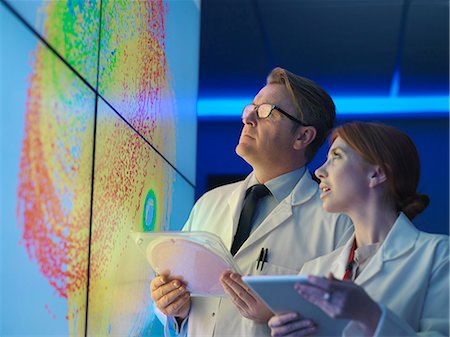 Scientists with silicon wafer studying graphical display of wafer on screens Stock Photo - Premium Royalty-Free, Code: 649-08085274