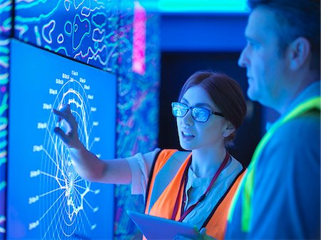 Female geologist with colleague studying graphical display of oil and gas bearing rock on screens Stock Photo - Premium Royalty-Free, Code: 649-08085276