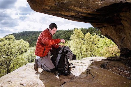 Young male hiker unpacking backpack on crocodile rock, Pateley Bridge, Nidderdale, Yorkshire Dales Stock Photo - Premium Royalty-Free, Code: 649-08085312