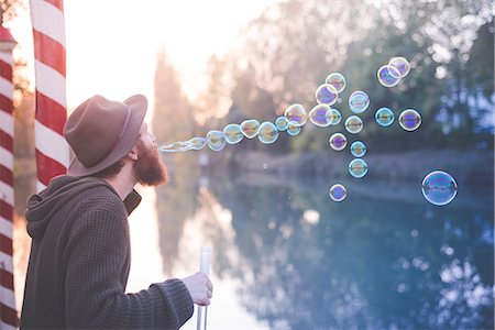 dreamy - Young man blowing bubbles Stock Photo - Premium Royalty-Free, Code: 649-08085387