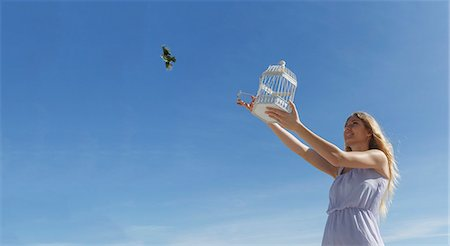 flying bird - Young woman releasing bird from cage toward blue sky Stock Photo - Premium Royalty-Free, Code: 649-08085443