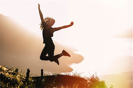 Silhouetted view of young woman jumping mid air at sunset above Lake Atitlan, Guatemala Stock Photo - Premium Royalty-Free, Code: 649-08085489