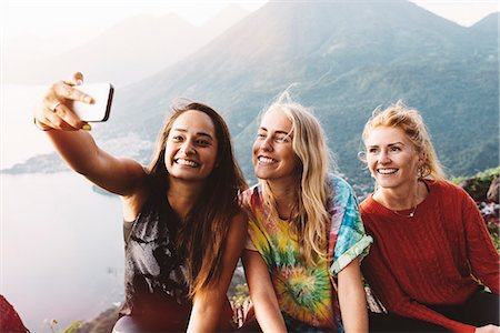 people and vacation - Three female friends taking smartphone selfie at Lake Atitlan, Guatemala Stock Photo - Premium Royalty-Free, Code: 649-08085482