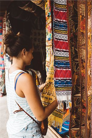 purchase - Young woman shopping for textiles at market stall,  Lake Atitlan, Guatemala Stock Photo - Premium Royalty-Free, Code: 649-08085496