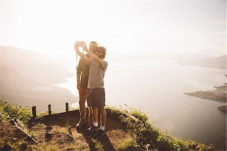 Two young men taking selfie at Lake Atitlan on digital camera, Guatemala Stock Photo - Premium Royalty-Free, Code: 649-08085491