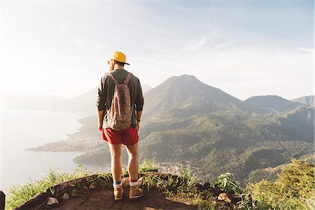 Rear view of young man looking out over Lake Atitlan, Guatemala Stock Photo - Premium Royalty-Free, Code: 649-08085492