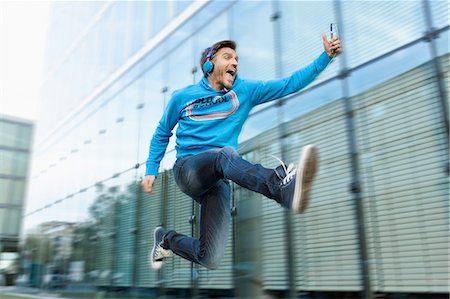 Mature man with headphones and smartphone jumping mid air on street Stock Photo - Premium Royalty-Free, Code: 649-08085738