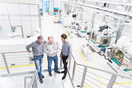 Engineers discussing notes on factory stairway Stock Photo - Premium Royalty-Free, Code: 649-08085777