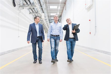 people working in factory - Three businessmen inspecting corridor in factory Stock Photo - Premium Royalty-Free, Code: 649-08085779