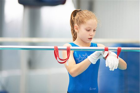 preteen girls stretching - Young gymnast using training wrist straps to aid practise on bars Stock Photo - Premium Royalty-Free, Code: 649-08085966