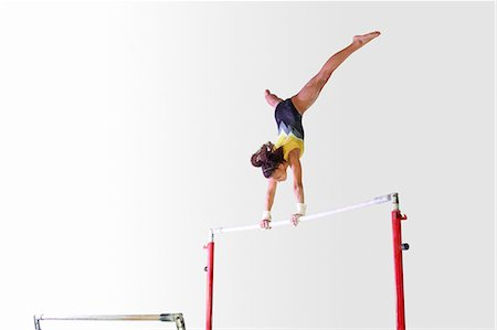 preteen girls gymnastics - Young gymnast performing on uneven bars Stock Photo - Premium Royalty-Free, Code: 649-08085962