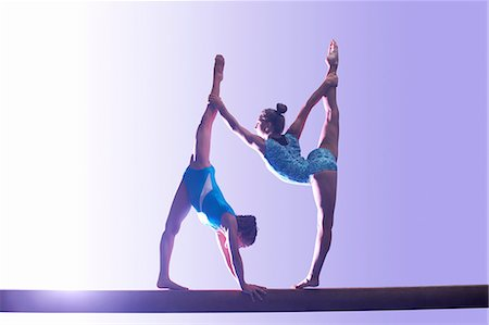 preteen girls stretching - Two young gymnasts performing on balance beam Stock Photo - Premium Royalty-Free, Code: 649-08085972