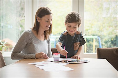 Boy smiling with mother as he paints on paper at table in living room Stock Photo - Premium Royalty-Free, Code: 649-08085988