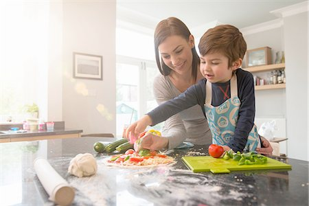 Mother and son preparing pizza together in kitchen Stock Photo - Premium Royalty-Free, Code: 649-08085996