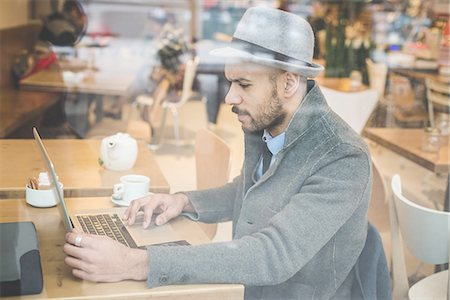 Businessman sitting in front of cafe window using laptop Stock Photo - Premium Royalty-Free, Code: 649-08086025