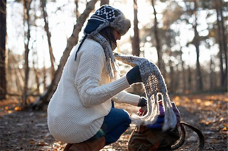 Mature female backpacker putting on scarf in forest Stock Photo - Premium Royalty-Free, Code: 649-08086091