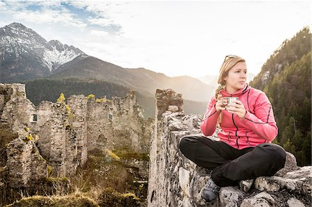 Young woman drinking coffee on top of Ehrenberg castle ruins, Reutte, Tyrol, Austria Stock Photo - Premium Royalty-Free, Code: 649-08086381