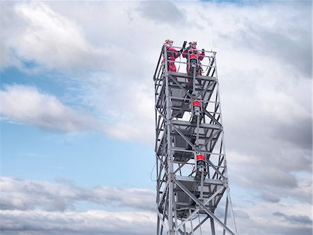 Two tower workers on offshore radio tower on windfarm, low angle view Stock Photo - Premium Royalty-Free, Code: 649-08086417